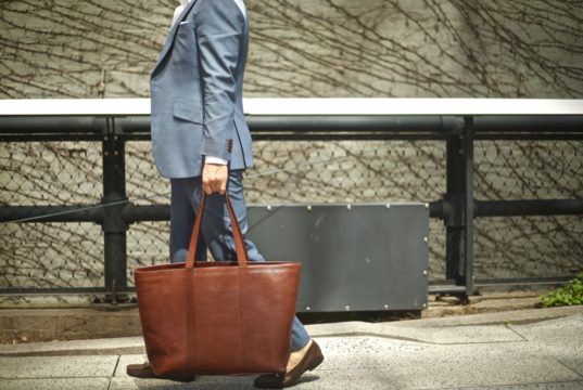 black lapel suit with jay butler brown leather tote bag